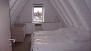 Großes Schlafzimmer mit Doppelbett und Kindergitterbett